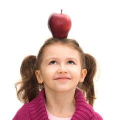 bimba con una mela in testa