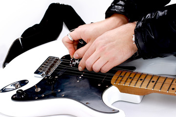 Person tuning a guitar from its headstock over white
