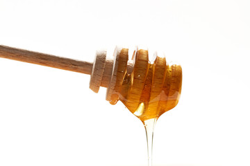 Golden honey on the wooden honey dipper on white background