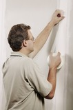 Man Putting Adhesive Tape On A Wall