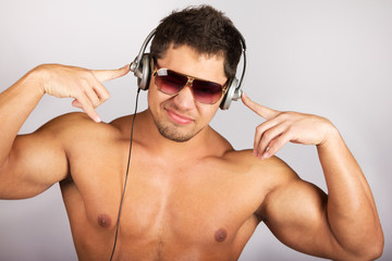 handsome man listening to music on headphone against natural bac