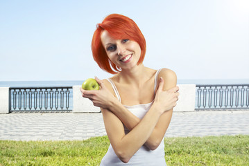 The beautiful smiling woman with an apple in a hand,outdoor