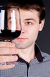 Man evaluating quality of  red wine