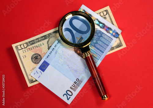 Detail of Twenty euro Bill Through a Magnifying Glass on red