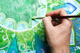 closeup of man painting green picture with circle pattern, manda