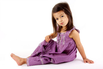 petite fille assise coquine sur fond blanc