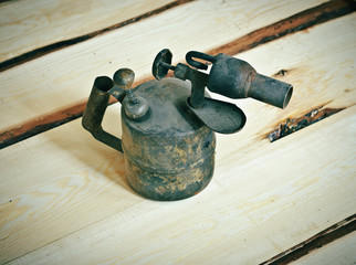 Old blowtorch on a wooden background