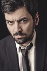 Uomo in giacca e cravatta con sguardo accigliato