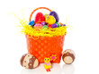cheerful easter eggs in straw in a plastic basket isolated over
