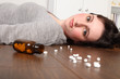 Wide eyed woman lying on floor with pills