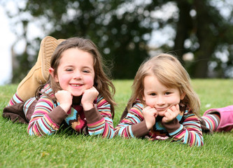 Sisters lying on grass smiling at camera