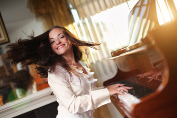 Pianist. Happy young woman playing piano indoors.