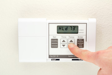 Hand on Thermostat