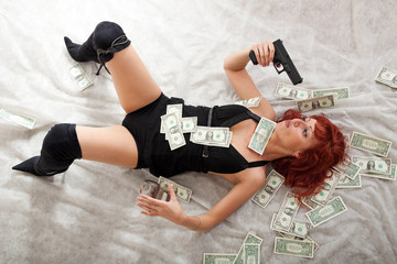 sexy young red-haired woman with gun and money