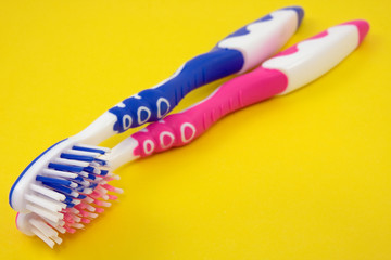 Two colorful tooth-brushes on a yellow background