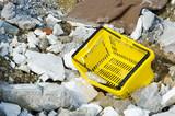 Shopping basket among rubble and rubish poster