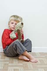 Lonely child sits on the floor holding his soft toy