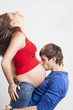 Man kissing his pregnant smiling wife at belly