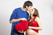 Man kissing his pregnant wife nose holding red heart