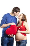 Happy joking couple embracing pregnant belly and red heart