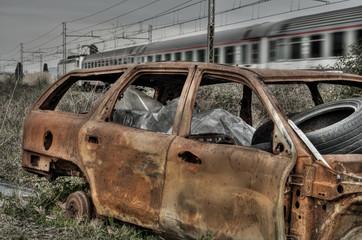 Auto bruciata e treno che passa