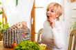 Woman with groceries eating carrot