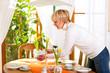 Frau deckt daheim den Kaffee Tisch