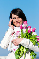 Portrait happy women with pink tulips talking by a cellular tele