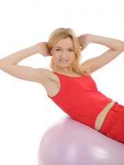 Pretty sporty fitness woman doing abs exercise with pilates ball