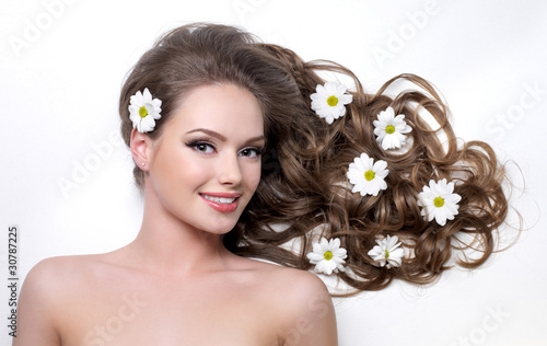 Smiling woman with camomiles in hair