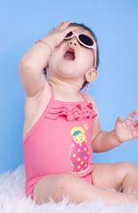 fillette de 8 mois jouant avec ses lunettes de soleil