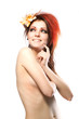 Portrait of beautiful naked woman with spring flower in hair on