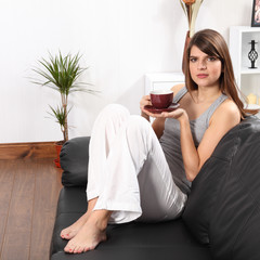 Beautiful woman at home on sofa drinking coffee