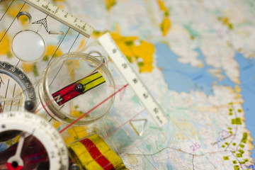 Different orienteering compasses over a blurred map