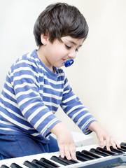 bambino con ciuccio suona tastiere