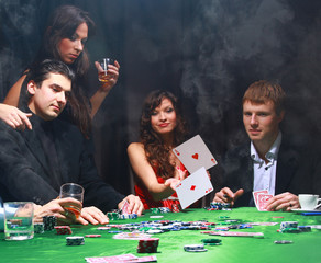 Stylish woman in black suit folds two cards in casino