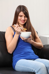 Cheerful woman at home eating breakfast cereal