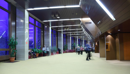 many people sitting, standing and walking in big light lobby