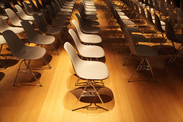 several rows of white plastic chairs with chromium-plated legs