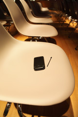 several rows of plastic chairs; smartphone with stylus on chair
