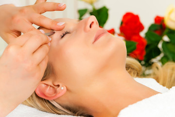 Frau im Kosmetikstudio bekommt die Augenbrauen gezupft