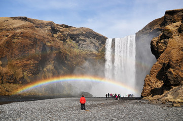 Skogafoss waterfall with rainbow a some tourists,Iceland