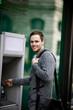 A young man using a cash machine