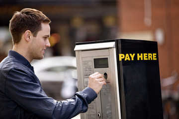 A young man putting coins in a parking meter