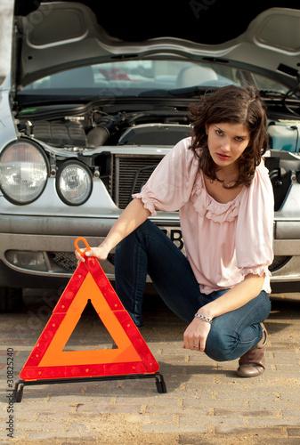 Frau mit Warndreieck vor Auto
