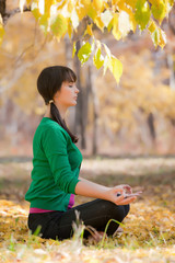 beautiful woman meditates in autumn park