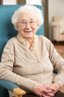 Senior Woman Relaxing In Chair At Home