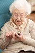 Senior Woman Dialling Number On Mobile Phone Sitting In Chair At