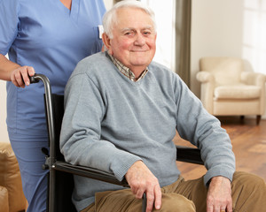 Disabled Senior Man Sitting In Wheelchair With Carer Behind