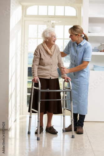 Carer Helping Elderly Senior Woman Using Walking Frame